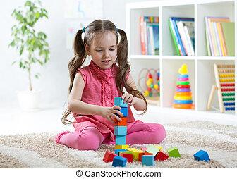 kind, meisje, spelend, met, blok, speelgoed, in, dagverzorging centrum