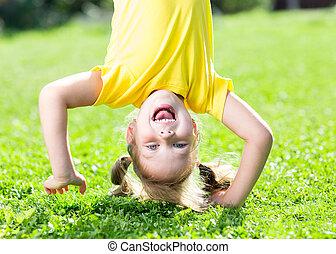 kind, meisje, staand, ondersteboven, op, haar, hoofd, gras, in, zomer