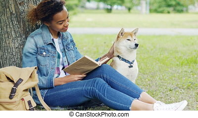 Kind mixed race woman is reading book in park and stroking her dog sitting on lawn under tree together. Intelligent hobby, caressing animals and youth concept.