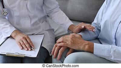 Kind nurse doctor comforting elderly female patient. - Focus...