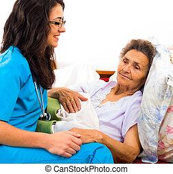 Kind Nurse with Elderly - Kind nurse easing elderly lady's...