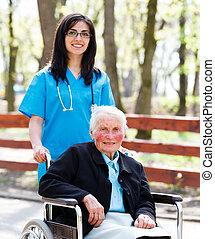 Kind Nurse With Elderly Lady In Wheelchair