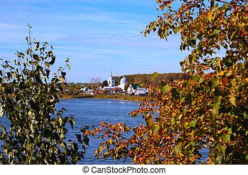 Kind on autumn village located lake