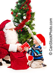 Kind Santa Claus presenting little boy with gift. Sitting together under Christmas tree