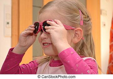 Kind setzt Sonnenbrille auf - Maedchen setzt rosa...