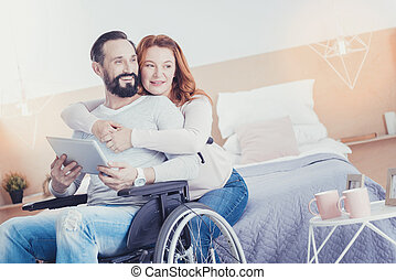 Kind wife hugging her disabled husband and feeling happy