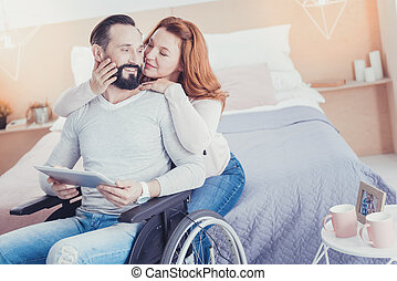 Kind wife looking at her husband in a wheelchair and smiling