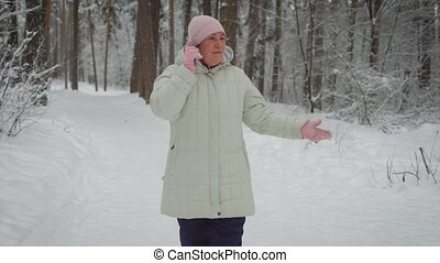 Kind woman, dressed in a bright pink hat and gloves, long white jacket with hood, black pants, fun talking friend on smartphone, telling what around the winter forest landscape, snowy paths.