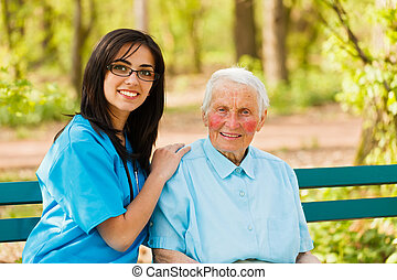 Kind elderly lady with caring nurse sitting both on bench in a park.