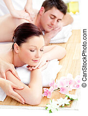 Kind young couple receiving a back massage in a spa center