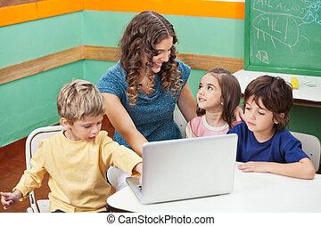kinder, laptop benutzend, während, lehrer, assistieren, sie