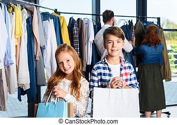 kinder, mit, einkaufstüten, in, kleiderladen