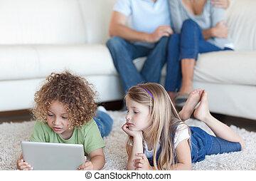 kinderen, gebruik, een, tablet, computer, terwijl, hun, ouders, zijn, schouwend, in, hun, woonkamer