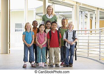 kindergärtnerin, stehende , mit, kinder, in, korridor