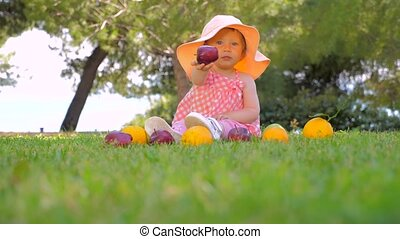 Kindergarten background. Healthy and cheerful child playing outdoor. Beautiful girl playing with fruits on the yard. Summer harvesting. Autumn harvest concept.