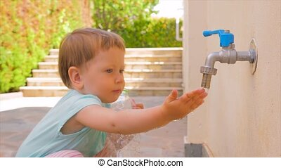 Kindergarten background. Pediatrics concept. Baby exploring the world. Pure water flowing on baby's hand. Developing tactile skills. Harmonious development of child. Water therapy for babies children
