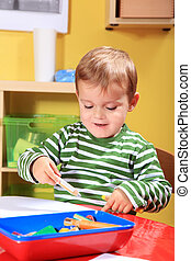 Kindergarten - Cute caucasian toddler drawing a picture in...