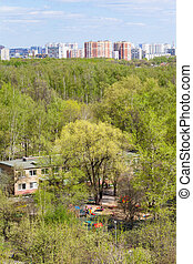 kindergarten in green woods and city in spring