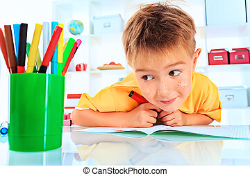 kindergarten - Little boy drawing in his notebook at home.