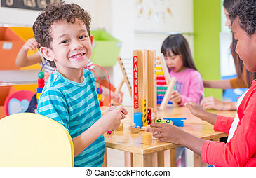 Kindergarten students smile when playing toy in playroom at preschool international,education concept