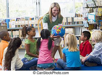 Kindergarten teacher and children looking at globe in library