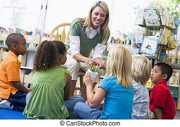 Kindergarten teacher and children looking at seedling in...