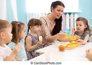 kindergarten teacher and preschoolers children have break for fruits and vegetables
