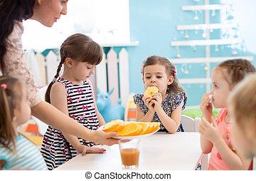kindergarten teacher and preschoolers kids having break for fruits and vegetables