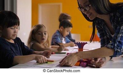Kindergarten teacher helping kids at art class - Lovely...