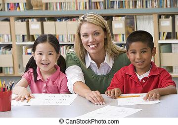 Kindergarten teacher helping students learn writing skills