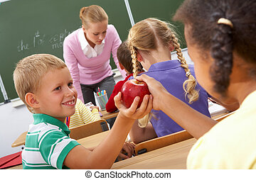 Kindness - Portrait of schoolgirl passing red apple to...