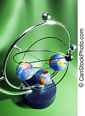 Kinetic Mobile with Globes on Green Background
