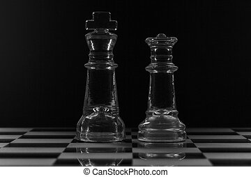 King and queen glass chess piece facing each other in black and white
