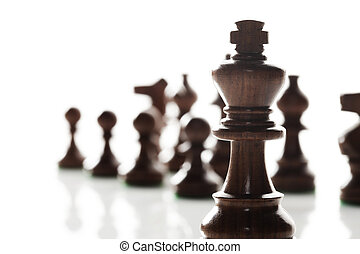 king chess piece with others in background. Low depth of field, focus on foreground.