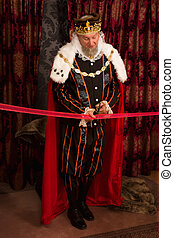 Royal king cutting a red ribbon with scissors