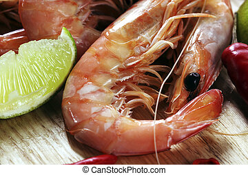 King prawns on a board, with lime and red chillies.