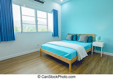 King-size bed in blue bright bedroom