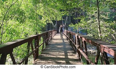 Woman walking on Suspension footbridge to Zumwalt Meadow. Zumwalt hiking in Kings Canyon National Park, a large clearing in the forest with wildflowers and the surrounding cliffs of Kings Canyon.