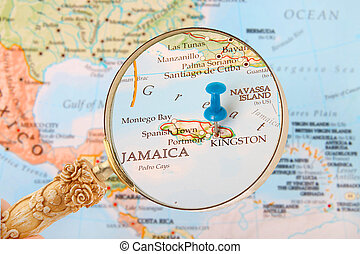 Blue tack on map of Caribbean with magnifying glass looking in on Kingston, Jamaica