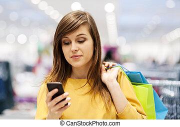 kisasszony, texting, képben látható, mobile telefon, alatt, bolt