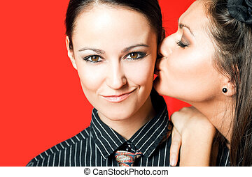 two women - one kissing other on the cheek, red background