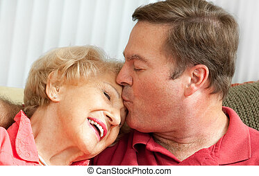 Kiss for Mom - Adult man kissing his elderly mother on the...