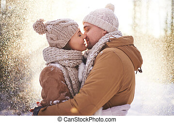 Kiss in snowfall - Happy young man and woman kissing in...