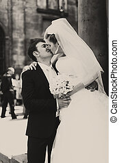 Kiss in the air - groom holds bride in arms