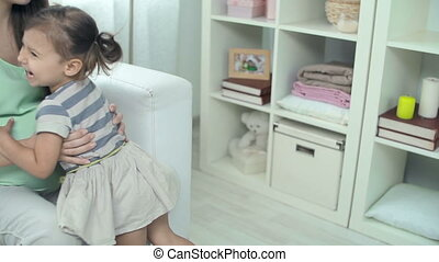 Kiss in the Tummy - Little girl hugging her mother expecting...
