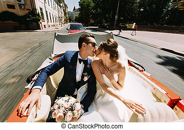 Kiss of the couple in the old-fashioned car