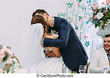 Kiss of the married couple on the wedding celebration