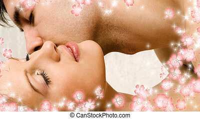kiss with flowers - kissing couple in bed surrounded by...