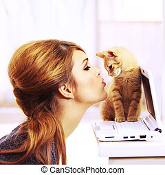 Gorgeous blond fashion model kissing a little cat's nose on a laptop notebook inside a beautiful home in the kitchen