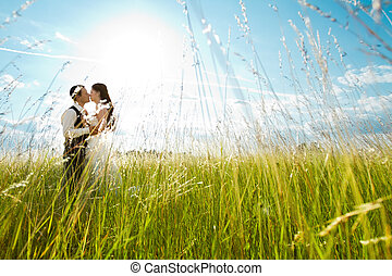 Beautiful bride and groom standing in grass and kissing. Wedding couple fashion shoot.